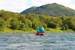 I turisti galleggiano sul fiume con una tenda blu sotto forma di vela fotografia stock