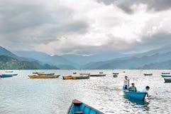 I turisti godono del giro della barca nel vasto lago Phewa, prima di forte temporale, colori naturali Fotografia Stock