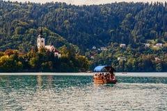 I turisti nuotano alla chiesa di St Mary sulla lama del lago in Slovenia in barca immagine stock