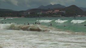 I turisti nuotano in forti onde del mare della Cina Meridionale sul video del metraggio delle azione della spiaggia di Dadonghai archivi video