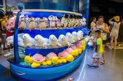 I turisti passano in rassegna i giocattoli molli in un negozio del museo Immagine Stock Libera da Diritti