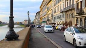 I turisti passeggiano lungo l'argine del fiume di Arno a Firenze stock footage