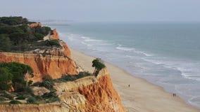 I turisti passeggiano lungo la spiaggia Falesia Vilamoura Portogallo stock footage