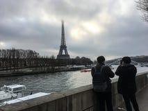 I turisti prendono le foto della torre Eiffel attraverso la Senna un giorno di inverno nuvoloso Fotografie Stock Libere da Diritti