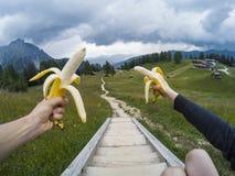 I turisti prendono un resto e babanas del cibo con una vista su paesaggio dei moutains delle dolomia e su una foresta di gree su  Fotografie Stock Libere da Diritti