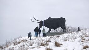 I turisti scalano alla scultura di un toro gigante Tarvas Rakvere, Estonia archivi video