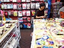 I turisti scelgono da vari prodotti del ricordo ad un deposito o ad un negozio in Chinatown, Singapore Immagini Stock Libere da Diritti