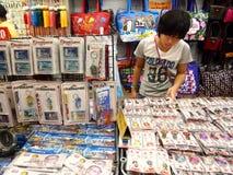I turisti scelgono da vari prodotti del ricordo ad un deposito o ad un negozio in Chinatown, Singapore Fotografia Stock Libera da Diritti