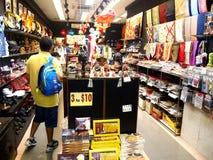 I turisti scelgono da vari prodotti del ricordo ad un deposito o ad un negozio in Chinatown, Singapore Immagine Stock