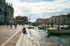 I turisti si siedono sui punti di Grand Canal, Venezia, vicino ai Di Santa Maria della Salute della basilica Immagini Stock Libere da Diritti