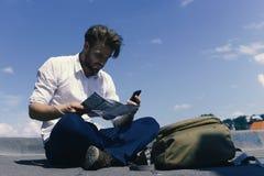 I turisti si sono persi l'esame della mappa e la tenuta del telefono Immagine Stock