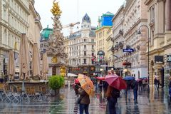 I turisti sotto gli ombrelli variopinti vanno un giorno piovoso lungo Graben fotografie stock