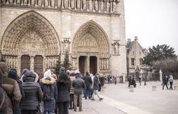 I turisti stanno nella linea alla cattedrale di Notre Dame, alcune camminano Immagine Stock