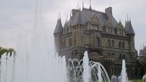 I turisti stanno sedendo vicino al castello nello stile medievale nel giorno di estate, fontana è al primo piano archivi video