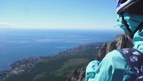 I turisti stanno sopra la montagna e l'esame del mare qui sotto, vista della parte posteriore video d archivio
