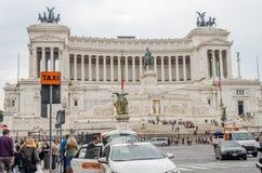 I turisti stranieri che passeggiano durante il giro e prendono le immagini vicino al monumento di Vittoriano sulla piazza Venezia Fotografia Stock Libera da Diritti