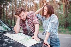 I turisti stupiti e frustrati stanno stando esterni e stanno guardando alla mappa Si sono persi il tipo stanno firmando la sua te Fotografie Stock