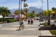 I turisti su un albero hanno allineato il viale con i negozi ed i caffè in Playa de Las Americhe nell'isola di Tenerife Fotografia Stock