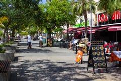I turisti su un albero hanno allineato il viale con i negozi ed i caffè in Playa de Las Americhe nell'isola di Tenerife Immagini Stock