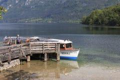 I turisti su una piccola barca in lago Bohinj, una destinazione famosa non lontano dal lago hanno sanguinato Fotografie Stock