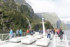 I turisti sulla barca gira nel fiordo di Milford Sound, isola del sud della Nuova Zelanda Fotografie Stock Libere da Diritti