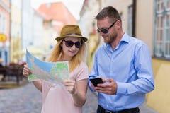 I turisti sulla città scattano usando la mappa della città e dello smartphone Immagine Stock Libera da Diritti