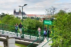 I turisti sulla stazione ferroviaria di funicolare Nebozizek che si dirige all'allerta di Petrin si elevano con la st Vitus Cathe Fotografia Stock Libera da Diritti
