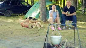 I turisti, un uomo e una donna stanno sedendo alla tenda, tè bevente e stanno guardando il giocatore di bocce appendere sopra il  stock footage