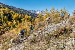 I turisti vanno su una campagna al lago Kardyvach La Russia, riserva caucasica di biosfera immagine stock