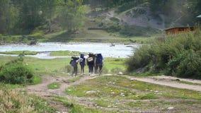 I turisti vanno trekking nelle montagne vicino al fiume della montagna archivi video