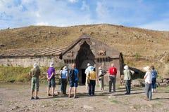 I turisti vicino al caravanserraglio della costruzione su Vardenyats passano Immagini Stock