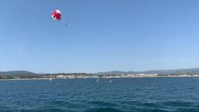 I turisti volano dal paracadute sopra il mare archivi video