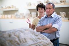 I turists maturi delle coppie esamina il bassorilievo della tomba in storico Fotografia Stock