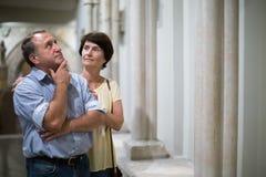 I turists maturi delle coppie esamina la mostra in museo Immagine Stock