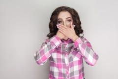 I tyst ` M, chockad flicka med den rosa rutiga skjortan, lockig hairst royaltyfria bilder