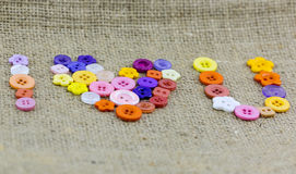 I❤U, I love you synonym made from colorful buttons. On old vintage fax canvas top view royalty free stock photos
