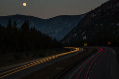I-70 Under a Full Moon. A long exposure shot of I-70 with a full moon rising over the mountains royalty free stock photography