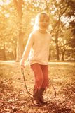 I use the sunny day for the play. Little girl in park holding jump rope royalty free stock photos