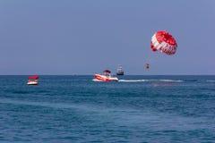 I vacanzieri volano su un paracadute dietro una barca su una vacanza estiva dal mare nella località di soggiorno fotografia stock libera da diritti