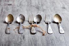 I vari cucchiai e forchette si sono intrecciati sulla tavola di legno rustica Immagini Stock