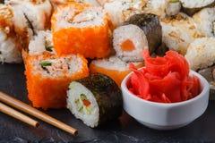 I vari generi di alimento dei sushi sono servito sulla pietra nera immagine stock
