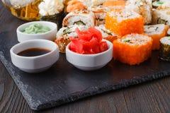 I vari generi di alimento dei sushi sono servito sulla pietra nera fotografie stock