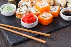 I vari generi di alimento dei sushi sono servito sulla pietra nera fotografia stock