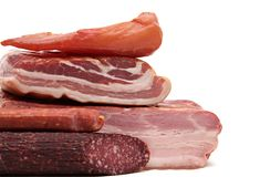 I vari prodotti a base di carne affumicati, la salsiccia, bacon hanno isolato il fondo bianco immagini stock