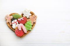 I vari tipi di biscotti decorativi del pan di zenzero di Natale su cuore di legno hanno modellato il piatto sulla vista bianca de immagine stock