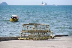 I vasi di granchio e dell'aragosta hanno impilato il peschereccio di cattura di rete da pesca sui precedenti dell'oceano della ba fotografia stock libera da diritti