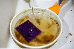 I vasken är en smutsig panna som fylls med vatten, närbild arkivbilder