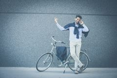 I`ve already arrived in front of the building. Businessman standing next to a bike and talking on the phone royalty free stock photo