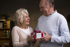 I've got a surprise for you!. Shot of an elderly couple exchanging gifts Royalty Free Stock Image