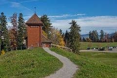 I vecchi alberi di autunno e della chiesa vicino montano Rigi, le alpi, Svizzera Immagine Stock